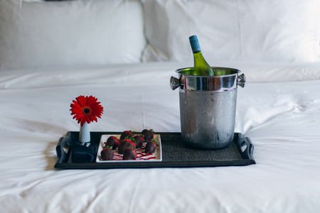 Chocolate covered strawberries on tray with wine and flower sitting on a bed Stock Photo