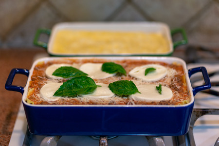 fresh lasagna in blue cookware sitting on top of a stove with basil leaves laid on top