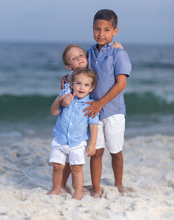 Three brothers embracing each other bare footed on a beach smiling and having fun