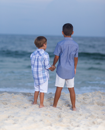 Two brothers holding hands on a beach facing away towards ocean bare feet in sand 版權商用圖片