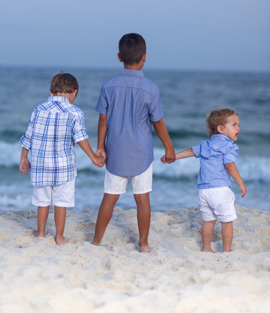 Three brothers holding hands on a beach facing away towards ocean bare feet in sand
