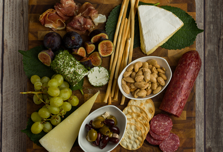 Cheese board flat lay shot with cheese, bread sticks, crackers, figs, grapes, goat cheese, brie cheese, almonds, nuts, and olives