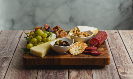Front view of a cheese board with with cheese, bread sticks, crackers, figs, grapes, goat cheese, brie cheese, almonds, nuts, and olives 版權商用圖片