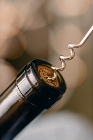 Close up photo of a wine bottle with cork screw and blurred out lights in background. shallow depth of field.
