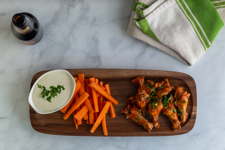 Hot chicken wings, carrots, and ranch dressing for dipping placed on a wood plate. 版權商用圖片
