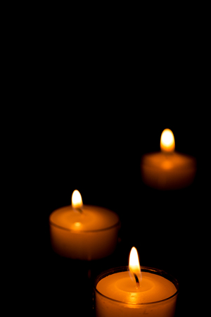 Three candles spaced apart in the dark.