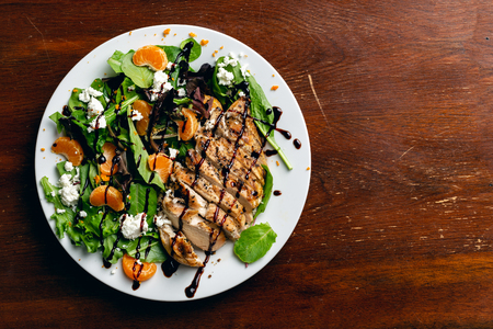 Grilled chicken salad with a glaze dressing, tangerines, orange zest, and goat cheese. Flat lay.