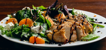 Grilled chicken salad with a glaze dressing, tangerines, orange zest, and goat cheese.