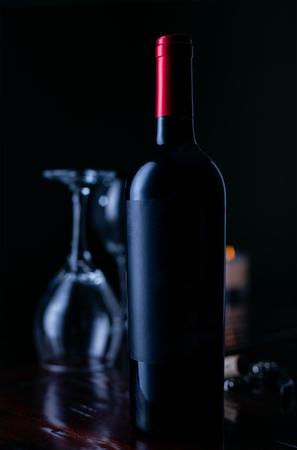 Red wine bottle with blank label on wood service with. wine glasses in background.