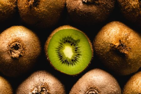 Kiwi Fruit flatlay background. One kiwi isolated amongst the others. 版權商用圖片