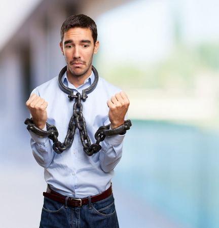 puppet master: Stressed businessman with chained hands Stock Photo