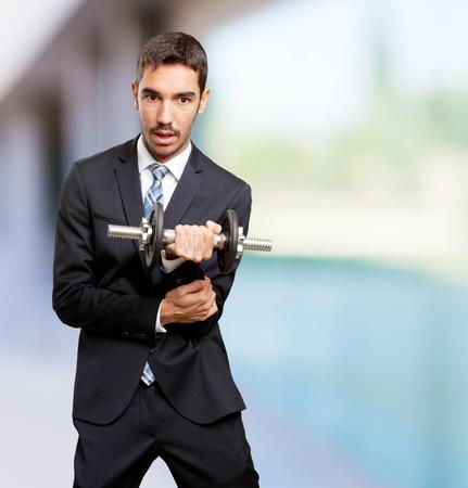 sad businessman: Sad businessman lifting a dumbbell