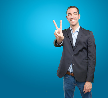 peace plan: Happy young businessman with victory gesture