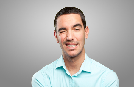 Close up of a young man winking an eye Stock Photo