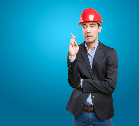 crossed fingers: Worried architect with crossed fingers gesture