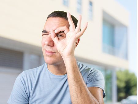 observe: Young man with observe gesture Stock Photo