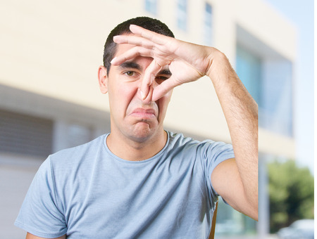 yuck: Young man with bad smell gesture