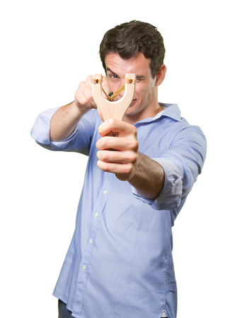 Concentrated guy using a slingshot on white background