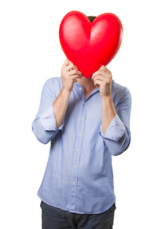 doctor holding gift: Young man holding a toy heart on white background Stock Photo