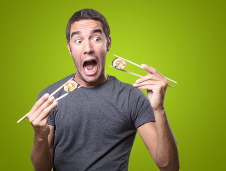 Surprised young man eating sushi on green background Stock Photo