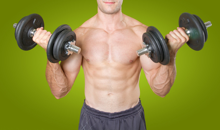 Strong man lifting a dumbbell on green background