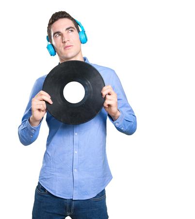 hombre joven dudosa usando auriculares Foto de archivo