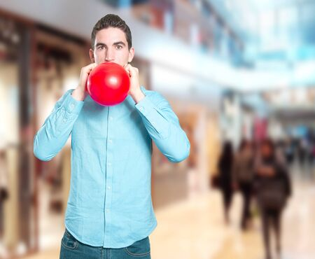 Surprised young man inflating a balloon Stock Photo