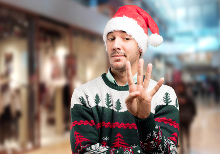 Surprised young man with four number gesture at Christmas Stock Photo