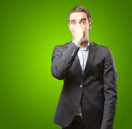 intolerable: Concerned businessman covering his nose