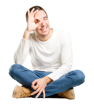 Seated young man with an observe gesture Stock Photo