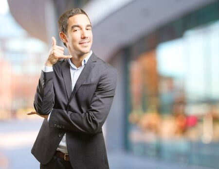 Satisfied businessman with a call gesture