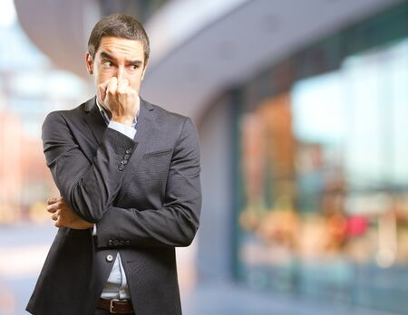 intolerable: Worried businessman covering his nose