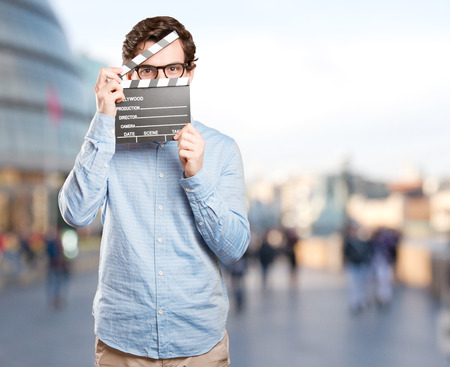 Happy young man using a clapperboard Stock Photo