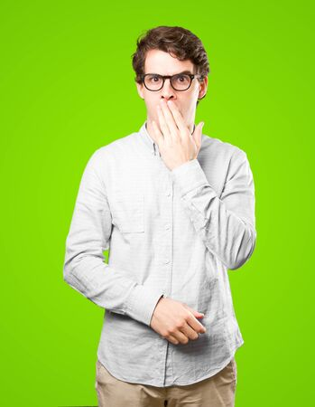 Astonished young man covering his mouth
