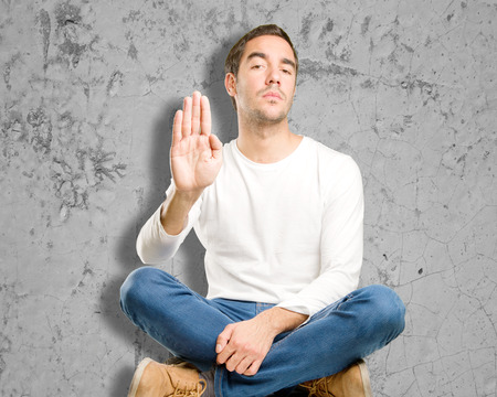 Seated young man with a stop gesture