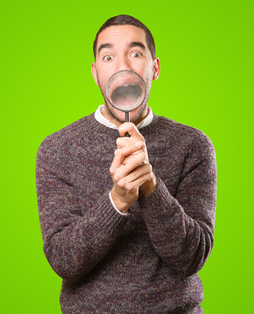 Surprised young man using a magnifying glass Stock Photo