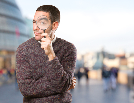 astonish: Surprised young man using a magnifying glass Stock Photo