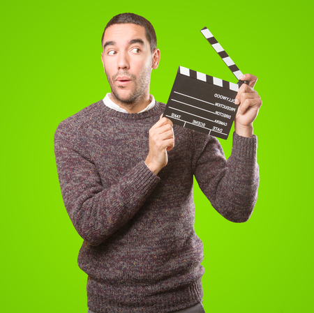 Funny young man using a clapperboard