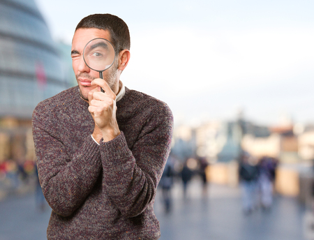 astonishing: Surprised young man using a magnifying glass Stock Photo