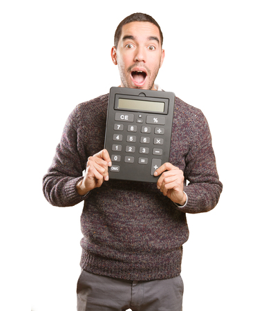 astonishing: Surprised young man holding a calculator