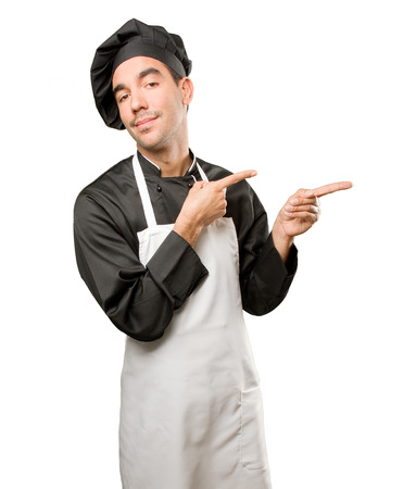 Pensive young chef pointing Stock Photo