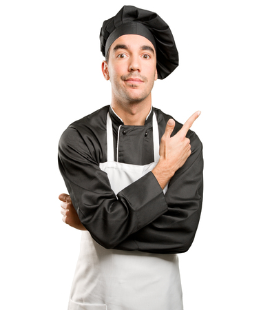 Confident young chef pointing Stock Photo