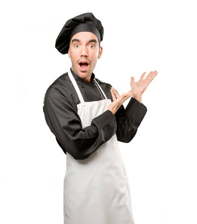 Surprised young chef welcoming