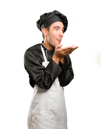 Happy young chef sending a kiss