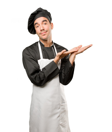 Satisfied young chef doing a show gesture Stock Photo