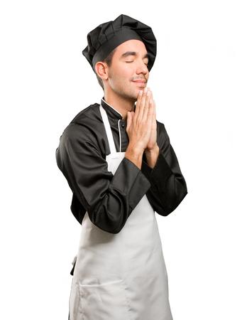 Hopeful young chef praying Stock Photo