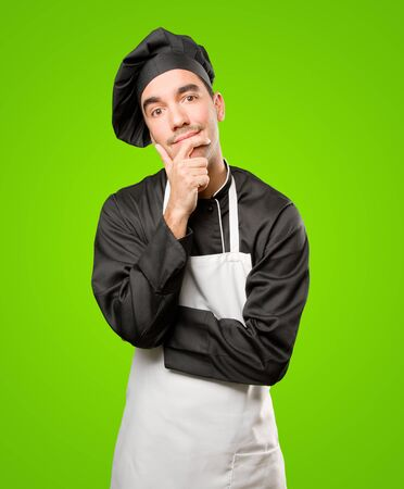 Happy young chef doubting