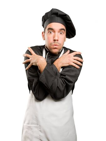 Concerned young chef with cold gesture Stock Photo