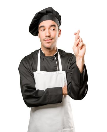 Doubtful chef doing finger cross gesture