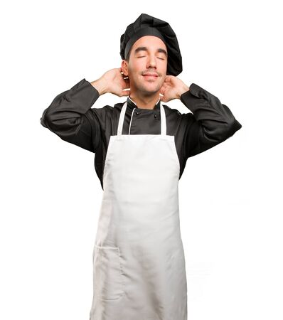 Happy young chef doing a relaxation gesture